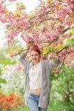 Mujer joven hermosa con el pelo rojo que se divierte que se coloca en árbol de la flor de cerezo Imágenes de archivo libres de regalías