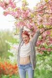 Mujer joven hermosa con el pelo rojo que se divierte que se coloca en árbol de la flor de cerezo Imagen de archivo libre de regalías