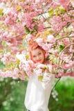 Mujer joven hermosa con el pelo rojo que se divierte que se coloca en árbol de la flor de cerezo Imagenes de archivo