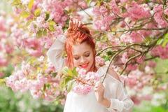 Mujer joven hermosa con el pelo rojo que se divierte que se coloca en árbol de la flor de cerezo Foto de archivo libre de regalías