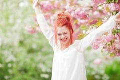Mujer joven hermosa con el pelo rojo que se divierte que se coloca en árbol de la flor de cerezo Imagen de archivo