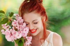 Mujer joven hermosa con el pelo rojo que se divierte que se coloca en el jardín con la rama de la flor de cerezo Imagenes de archivo