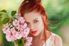 Mujer joven hermosa con el pelo rojo que se divierte que se coloca en el jardín con la rama de la flor de cerezo Fotografía de archivo