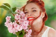 Mujer joven hermosa con el pelo rojo que se divierte que se coloca en el jardín con la rama de la flor de cerezo Imagen de archivo