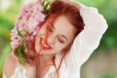 Mujer joven hermosa con el pelo rojo que se divierte que se coloca en el jardín con la rama de la flor de cerezo Foto de archivo