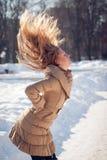 Mujer joven hermosa con el pelo rubio del vuelo el día de invierno Foto de archivo