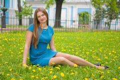 Mujer joven hermosa que se sienta en prado de la primavera fotografía de archivo