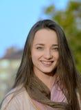 Mujer joven hermosa con el pelo rubio que sonríe afuera Foto de archivo libre de regalías