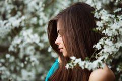 Mujer joven hermosa con el pelo sano largo que se relaja en el parque del flor Imágenes de archivo libres de regalías