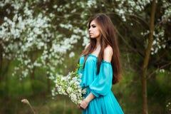 Mujer joven hermosa con el pelo sano largo que se relaja en el parque del flor Foto de archivo libre de regalías