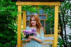 Mujer joven hermosa con el ramo de lila en jardín de la primavera Fotos de archivo