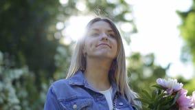 Mujer joven hermosa con el ramo de penies en parque almacen de metraje de vídeo