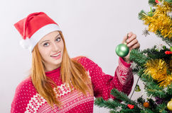 Mujer joven hermosa con el sombrero de Papá Noel que adorna el árbol de navidad. Imagenes de archivo