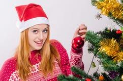 Mujer joven hermosa con el sombrero de Papá Noel que adorna el árbol de navidad. Imágenes de archivo libres de regalías