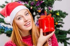 Mujer joven hermosa con el sombrero de Papá Noel que sonríe llevando a cabo un regalo de Navidad. Imagen de archivo