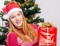 Mujer joven hermosa con el sombrero de Papá Noel que sonríe llevando a cabo un regalo de Navidad grande. Fotografía de archivo libre de regalías