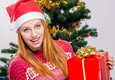 Mujer joven hermosa con el sombrero de Papá Noel que sonríe llevando a cabo un regalo de Navidad grande Imagen de archivo