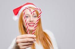 Mujer joven hermosa con el sombrero de Papá Noel que sonríe sosteniendo los bastones de caramelo en forma de un corazón. Foto de archivo libre de regalías