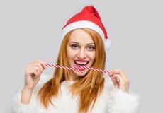 Mujer joven hermosa con el sombrero de Papá Noel que sonríe sosteniendo un bastón de caramelo en frente Foto de archivo libre de regalías