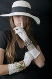 Mujer joven hermosa con el sombrero flojo elegante, los guantes del vintage largo y la joyería blancos Foto de archivo