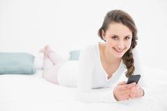 Mujer joven hermosa con el teléfono móvil en cama Foto de archivo