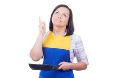 Mujer joven hermosa con freír a Pan Thinking What para preparar f Foto de archivo libre de regalías