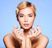 Mujer joven hermosa con hielo en sus manos Fotografía de archivo libre de regalías