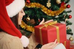 Mujer joven hermosa con la actual caja en el sombrero de santa en la Navidad Fotografía de archivo libre de regalías