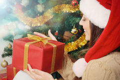 Mujer joven hermosa con la actual caja en el sombrero de santa en la Navidad Foto de archivo