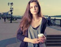 Mujer joven hermosa con la bebida caliente en la taza de papel disponible, coffe para llevar en manos, con el espacio de la copia Imagenes de archivo