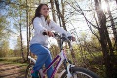 Mujer joven hermosa con la bicicleta de la montaña en bosque de la primavera Fotografía de archivo