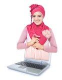 Mujer joven hermosa con la bufanda rosada fuera del ordenador portátil Foto de archivo libre de regalías