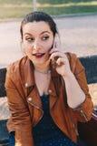 Mujer joven hermosa con la chaqueta de cuero que habla en el teléfono elegante del teléfono elegante en un parque de la ciudad qu foto de archivo libre de regalías