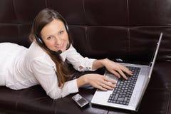 Mujer joven hermosa con la computadora portátil, el teléfono celular y Imagenes de archivo