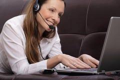 Mujer joven hermosa con la computadora portátil, el teléfono celular y Foto de archivo