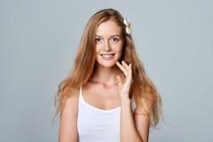 Mujer joven hermosa con la flor en pelo Fotografía de archivo libre de regalías