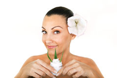 Mujer joven hermosa con la flor en una crema del pelo y del cosmético Fotos de archivo