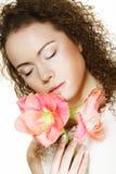 Mujer joven hermosa con la flor rosada sobre el fondo blanco imagen de archivo