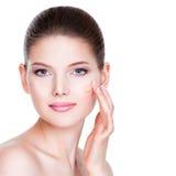 Mujer joven hermosa con la fundación cosmética en una piel Fotos de archivo libres de regalías