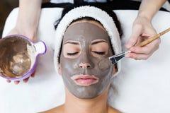 Mujer joven hermosa con la máscara facial de la arcilla en balneario de la belleza Detox fotos de archivo libres de regalías