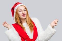 Mujer joven hermosa con la mirada sonriente del sombrero de Papá Noel al lado Imagen de archivo