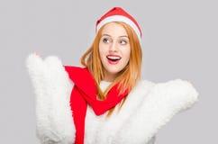 Mujer joven hermosa con la mirada sonriente del sombrero de Papá Noel al lado sorprendido Imágenes de archivo libres de regalías