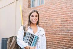 Mujer joven hermosa con la mochila y los libros Foto de archivo libre de regalías