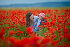Mujer joven hermosa con la muchacha del niño en campo de la amapola familia feliz que se divierte en naturaleza retrato al aire l imágenes de archivo libres de regalías