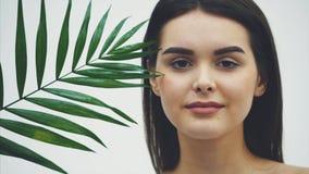 Mujer joven hermosa con la piel perfecta y el maquillaje natural que plantean el frente de una planta el verde tropical deja el f metrajes