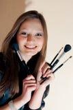 Mujer joven hermosa con la sonrisa de los cepillos del maquillaje Fotografía de archivo libre de regalías