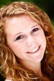 Mujer joven hermosa con la sonrisa del pelo rizado Fotos de archivo libres de regalías