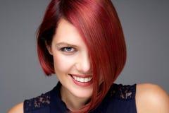Mujer joven hermosa con la sonrisa roja del pelo Foto de archivo