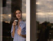 Mujer joven hermosa con la taza de café que mira a través de la ventana Fotos de archivo libres de regalías