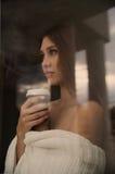 Mujer joven hermosa con la taza de café que mira a través de la ventana Imagen de archivo libre de regalías